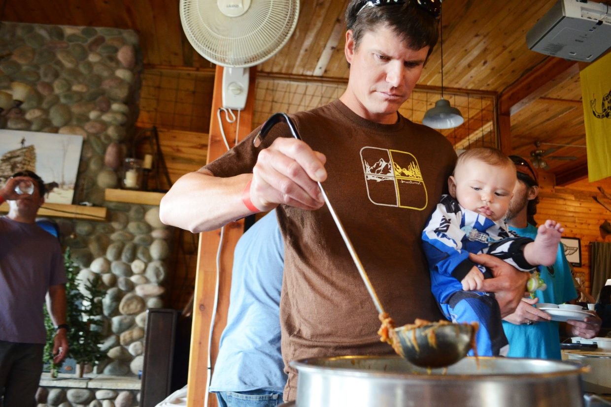 Nathan Reynolds and 6-month-old Isaac Reynolds grab a scoop of shredded beef chili at Sunday's 13th Annual Great North Routt Chili Cook Off at Hahn's Peak Roadhouse.