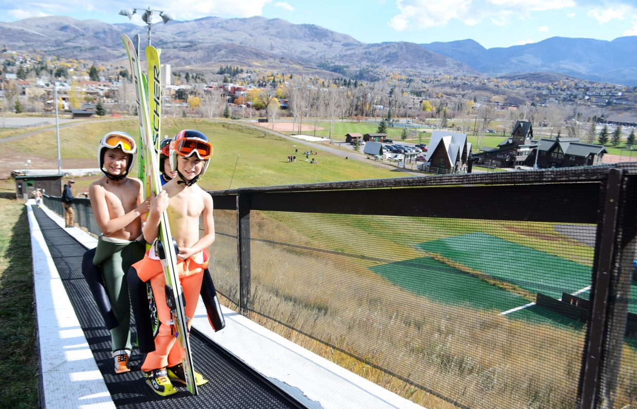Steamboat Springs Winter Sports Club ski jumpers Erik Belshaw, Gunnar Gilbertson and Bridger Carlton head up the magic carpet toward the top of the jumps at Howelsen Hill on Sunday. Other jumpers were on hand for the club's annual mini camp before cargo nets were placed on the jumps in preparation for the soon-to-come snow.