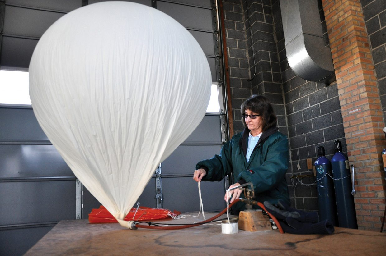 Becky Klenk inflates a giant latex weather balloon inside a cold garage. The Weather Service launches two balloons per day at 4 a.m. and 4 p.m. to gather the most up-to-date atmospheric conditions. Simultaneous launches at other officers across the country help to paint a picture of what the weather is doing.