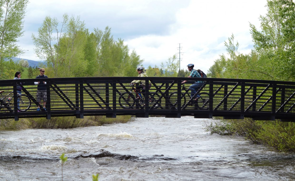 Some cyclists traverse the bridge across the Yampa River near Dr. Rich Weiss Park in downtown Steamboat Springs. A few showers on the eve of Memorial Day didn't stop Steamboat residents and visitors from biking and walking local trails.