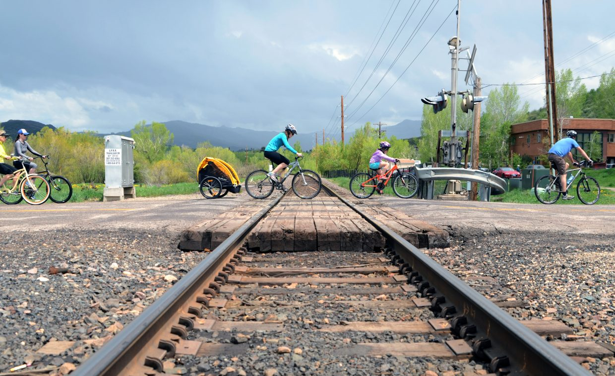 A family crosses the train tracks near the Yampa River Botanic Park on the eve of Memorial Day. Some Sunday showers didn't stop Steamboat Springs residents and visitors from hitting the trails on foot or bike.