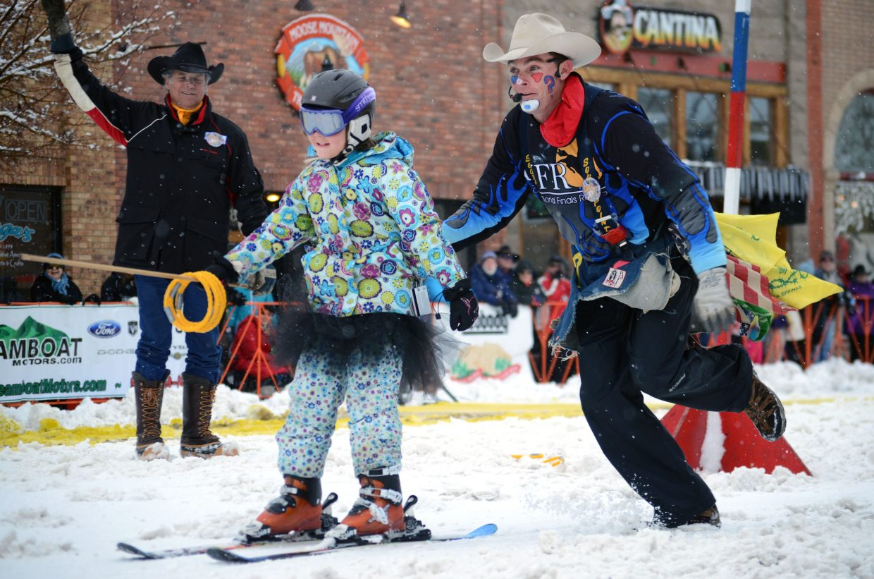 Allison Alfone, 8, couldn't hang on to the rope during the ring and spear event at the 101st Winter Carnival on Sunday, but carnival clown J.W. Winklepleck pushed her across the finish line.