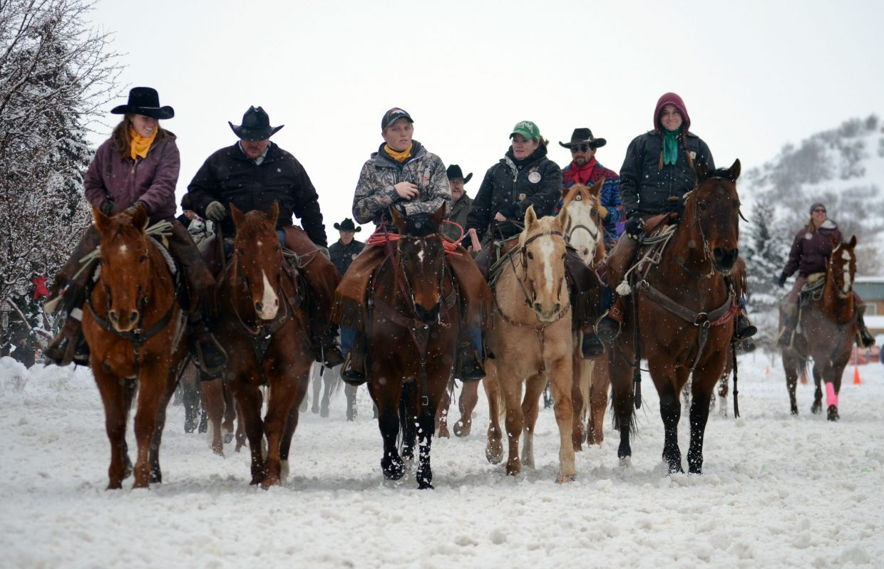 The horses and their riders for Sunday's street events make their way back toward the start line during the 101st Winter Carnival.