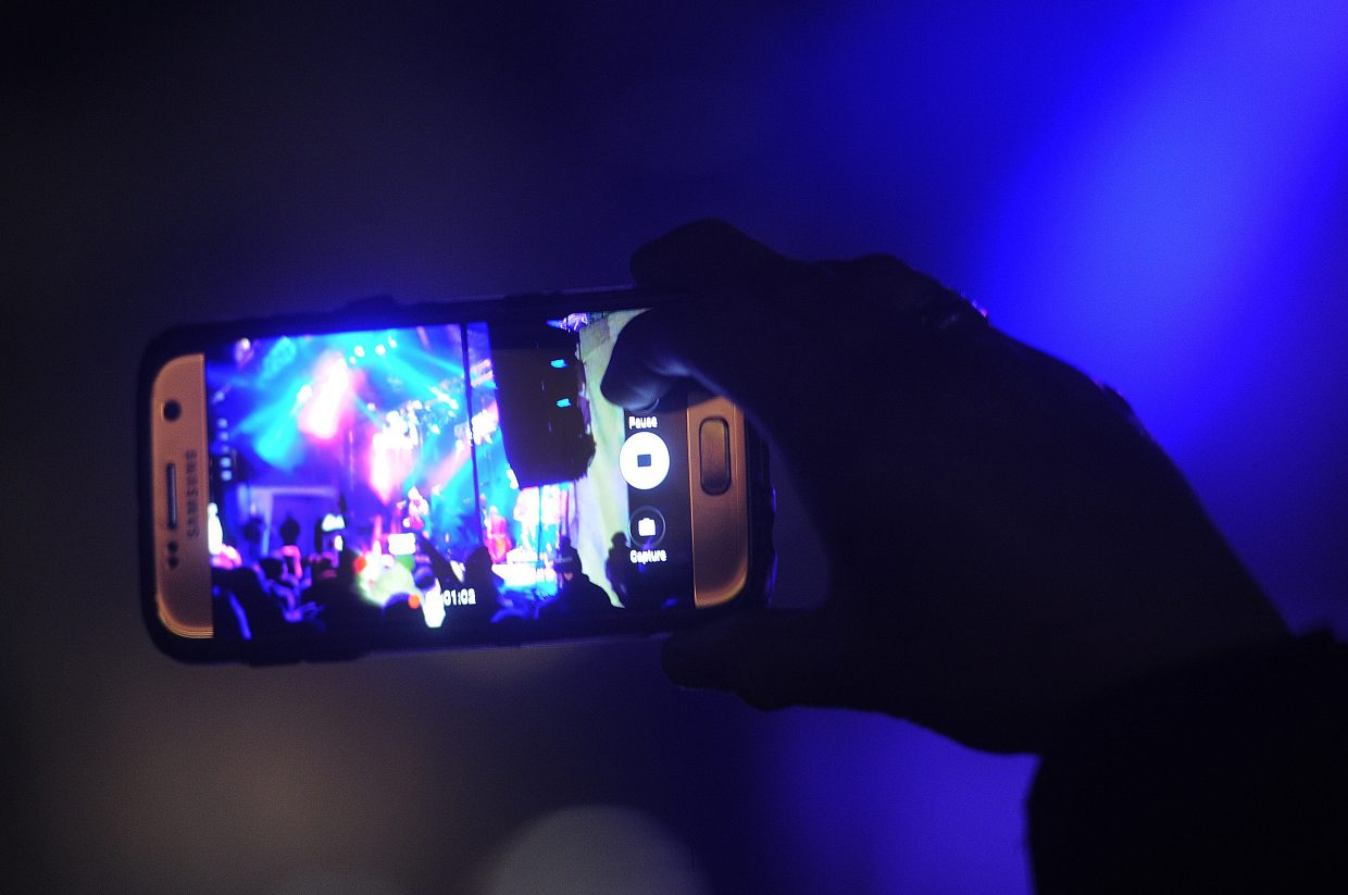 A spectator records a video of the WinterWonderGrass music festival on Friday night.