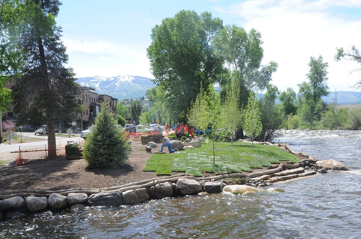 Landscapers put down sod and plant trees at the new Workman Park on Yampa Street in the summer.