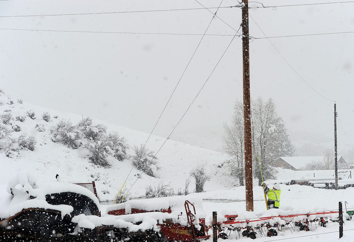 A Yampa Valley Electric Association employee works to isolate a problem with a power line off Routt County Road 44. Heavy snow Friday morning caused numerous power outages in the area.