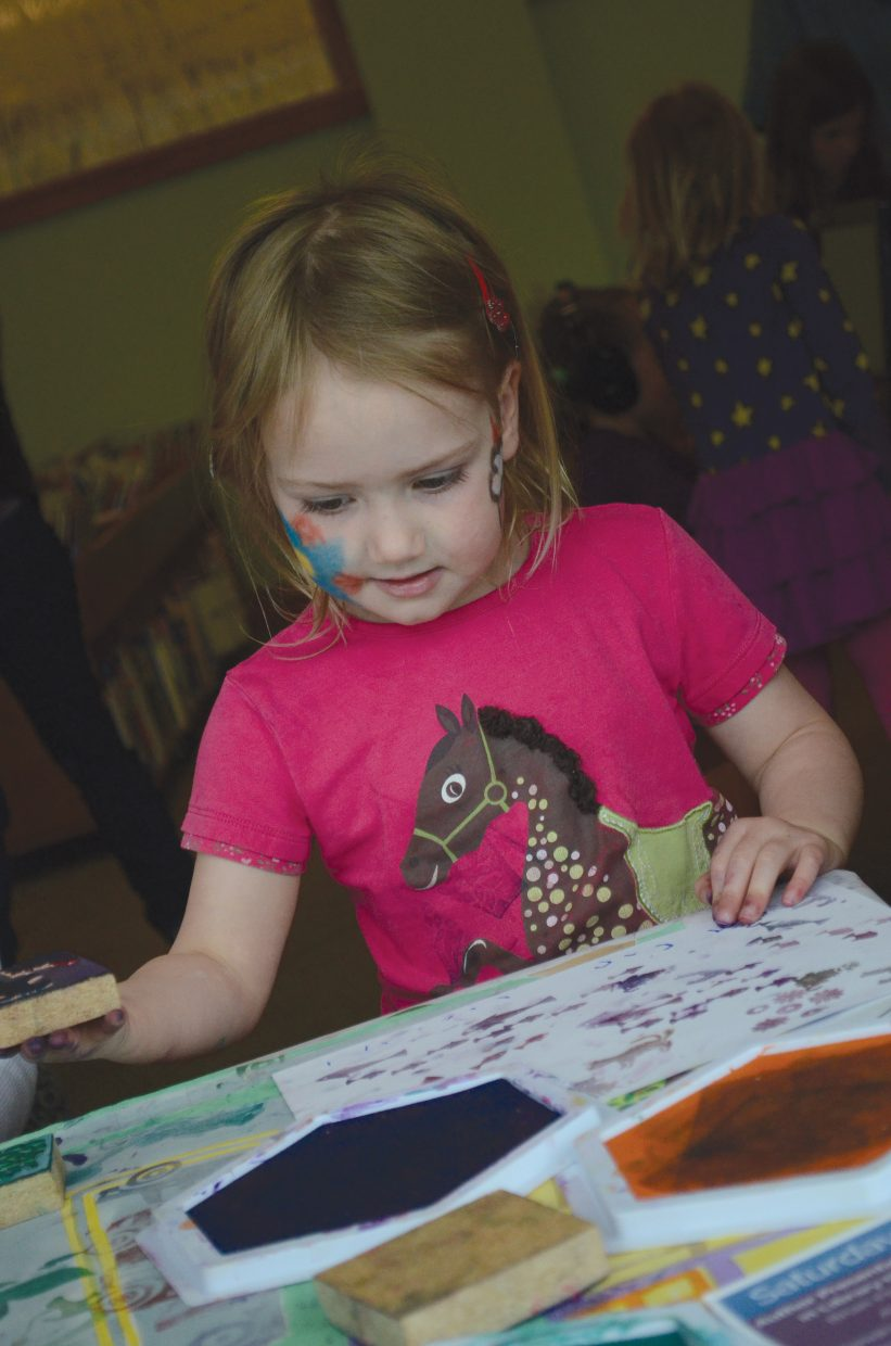 Sasha Kilbane is busy using colored ink and stamps to create works of art during the 2015 Children's Book Feast event at Bud Werner Memorial Library. The all-day literary arts event is a collaborative project of the library, Off the Beaten Path bookstore, Steamboat Springs Arts Council and Steamboat Springs School District.