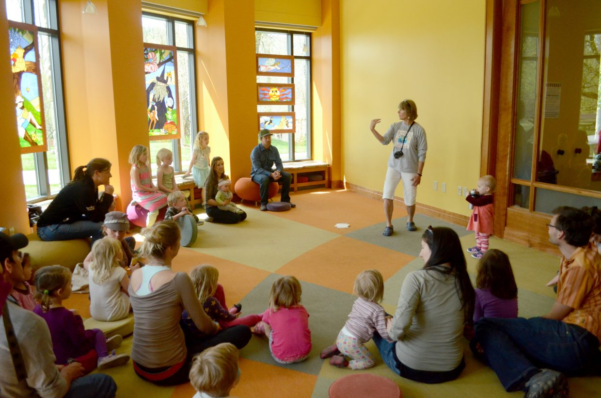Sherry Holland, who leads the Spellbinders volunteer storytelling group, entertains her young audience with a tale about bubble gum and a rattlesnake during the 2015 Children's Book Feast.