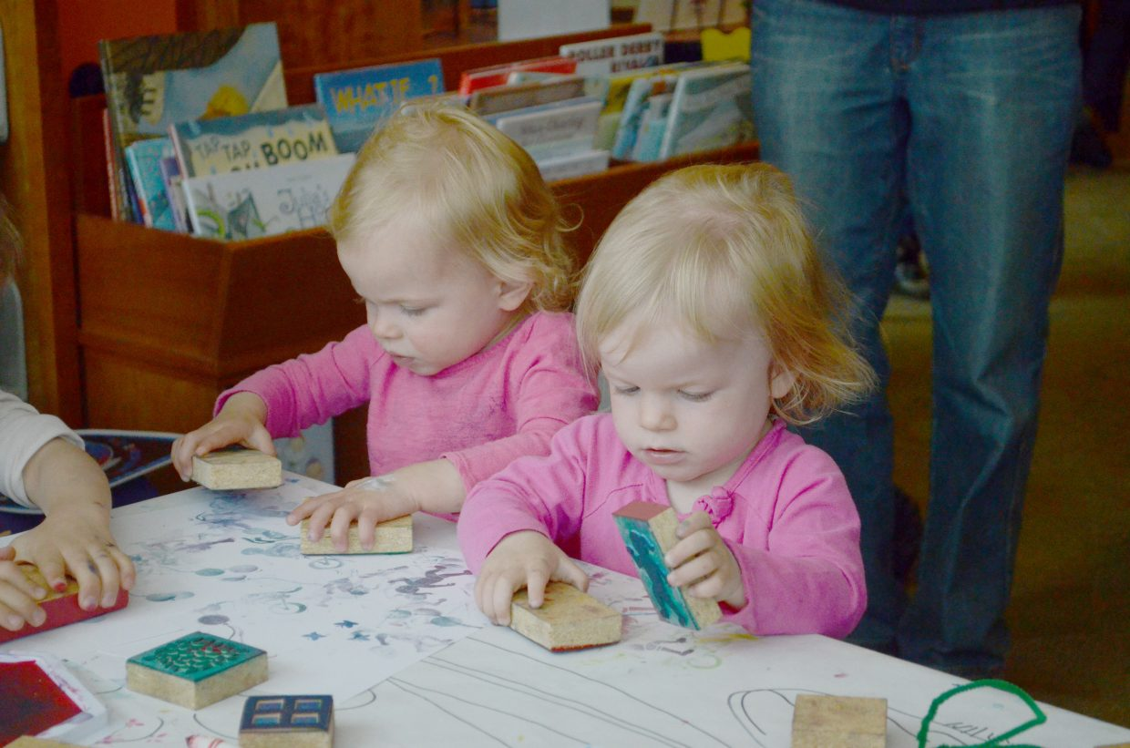 Twins Emma and Madeline Walsh, 2, enjoy creating stamp art Saturday during one of the Creative Fair activities offered during the day-long Children's Book Feast literary event, held Saturday at Bud Werner Memorial Library and the Depot Art Center.