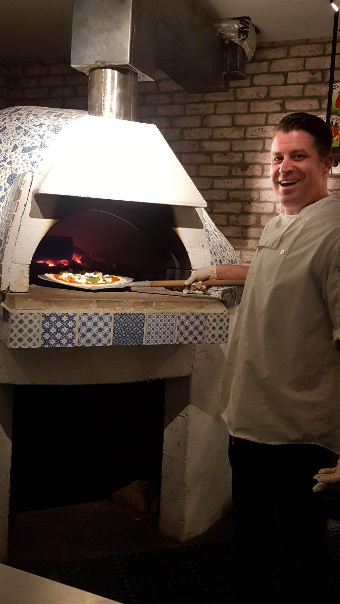 Brick owner and chef Lee Demusis stands outside the oven he built for creating mouth-watering wood-fired pizza.