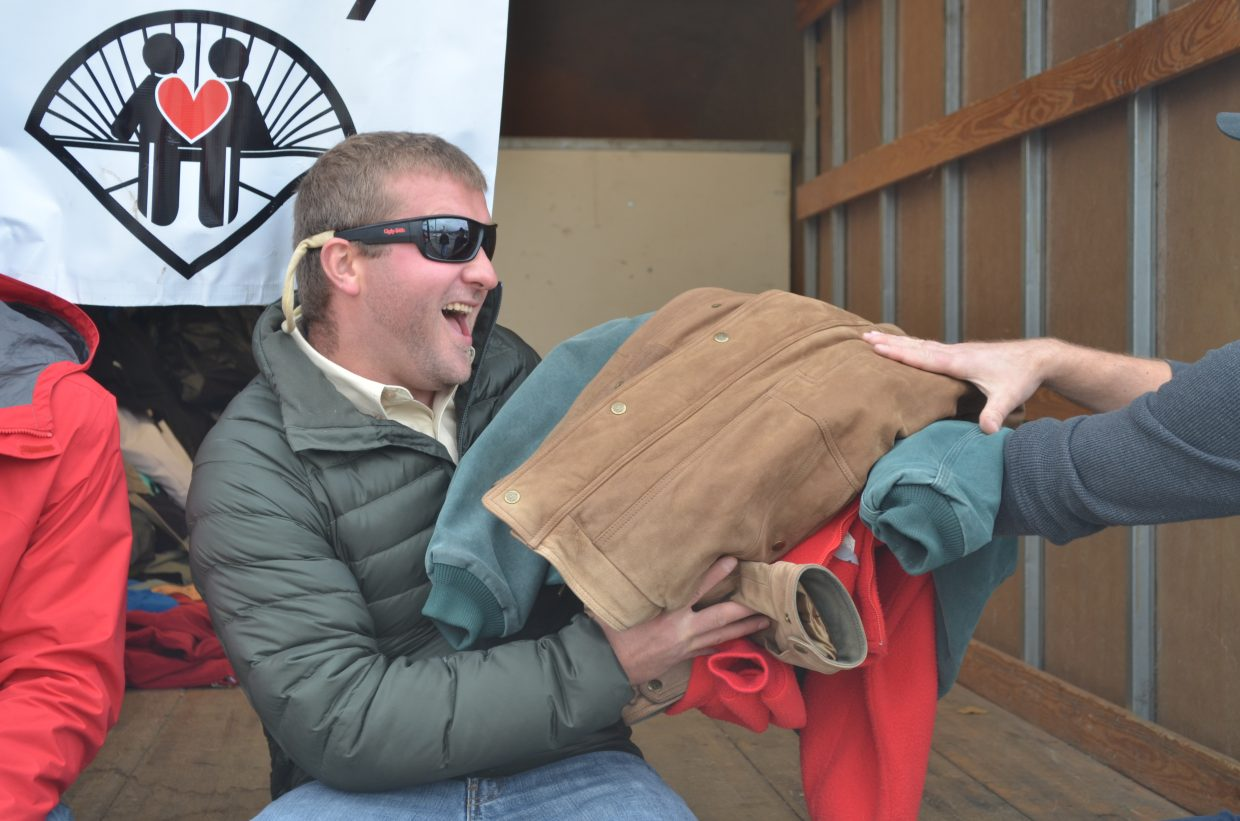 Zachary Chelberg helps collect coats during the Coat Drive for Lift-Up of Routt County at Natural Grocers. Volunteers gathered more than 800 coats.