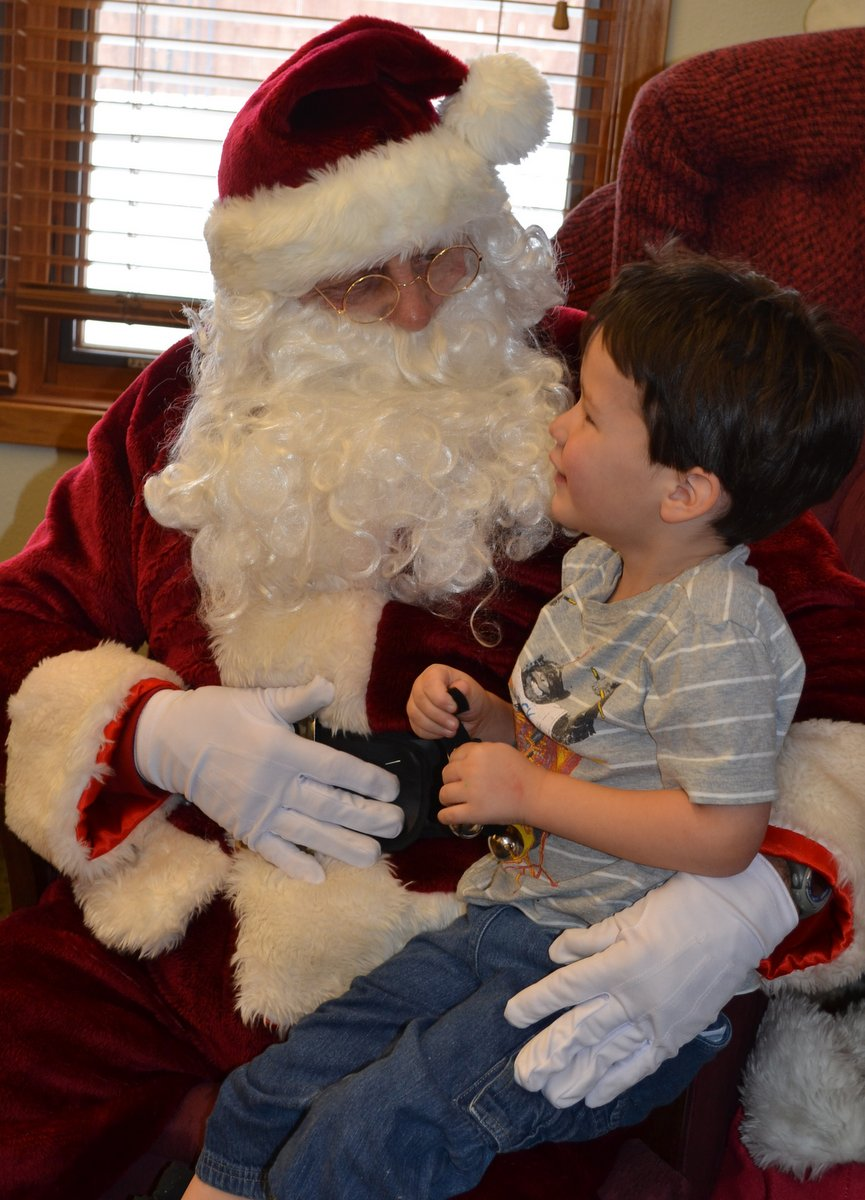 Jackson Steele sits with Mr. Claus at the Hayden Library's Santa Story Hour on Friday.