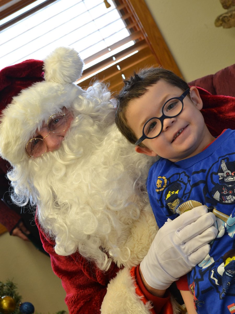 Carden Cucuel sits with Mr. Claus at the Hayden Library's Santa Story Hour on Friday.