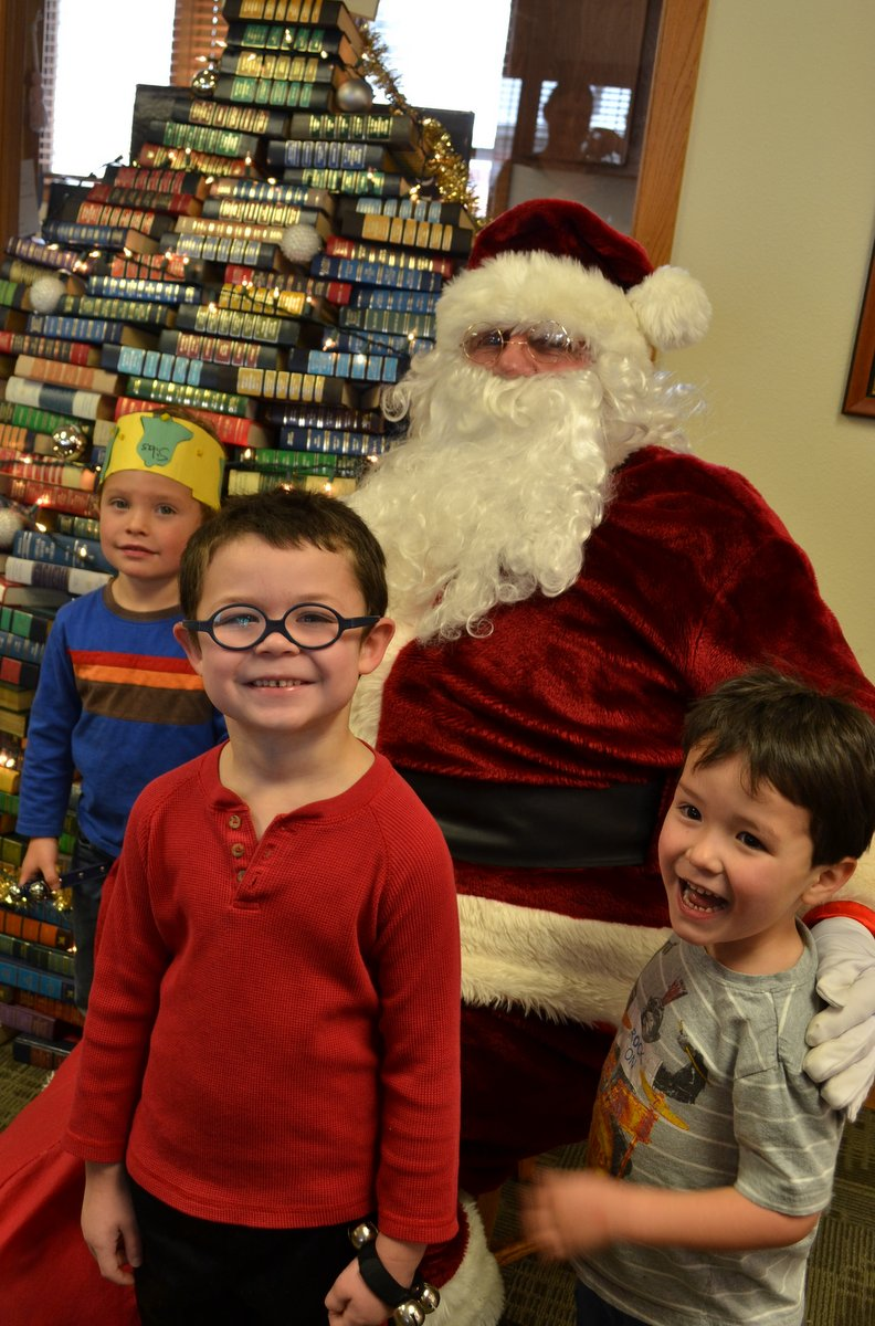 Silas Morrison, Carden Cucuel and Jackson Steele sit with Mr. Claus at the Hayden Library's Santa Story Hour on Friday.