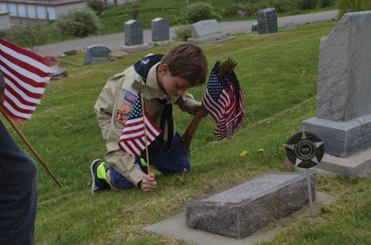 Noah Heckel, with Boy Scout Troop 194, places a flag on the grave of a Steamboat Springs military veteran in preparation for Monday's Memorial Day Service. Heckel was working with fellow Scouts Winston Vaughan, Justin Peretz, Aaron Peterson and Assistant Scoutmaster John Paulus to place the flags Thursday afternoon.