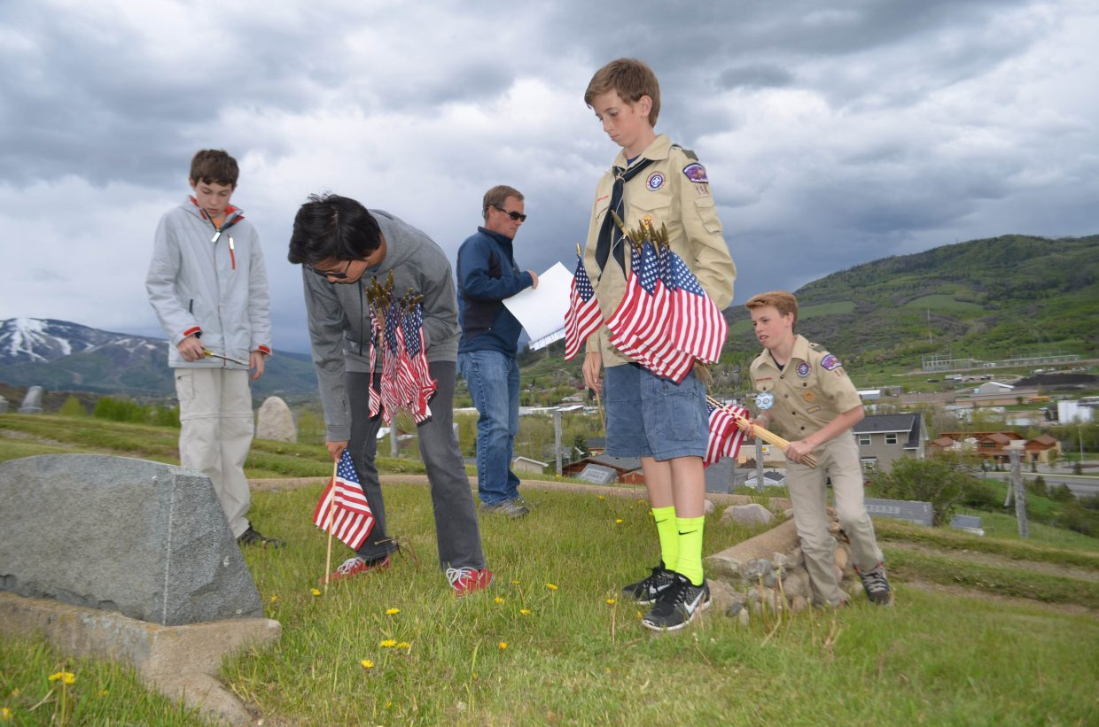Members of Boy Scout Troop 194 place flags on the graves of local military veterans at Steamboat Springs Cemetery Thursday afternoon in preparation for Monday's Memorial Day Service. From left: Aaron Peterson, Justin Peretz, Assistant Scoutmaster John Paulus, Noah Heckel and Winston Vaughan.