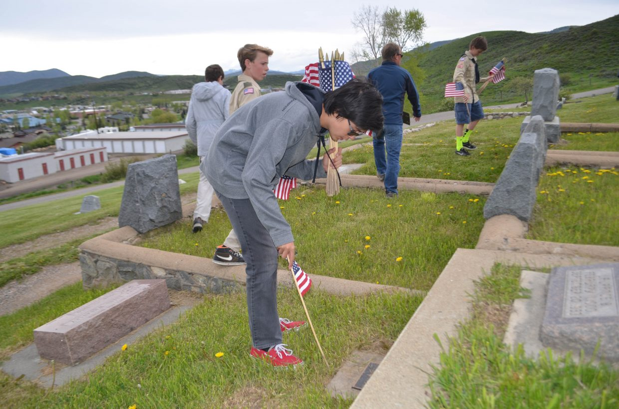 Local Boy Scout Justin Peretz places a flag on the grave of a local veteran. Members of Boy Scout Troop 194 were placing the flags Thursday afternoon in preparation for Monday's Memorial Day Service.