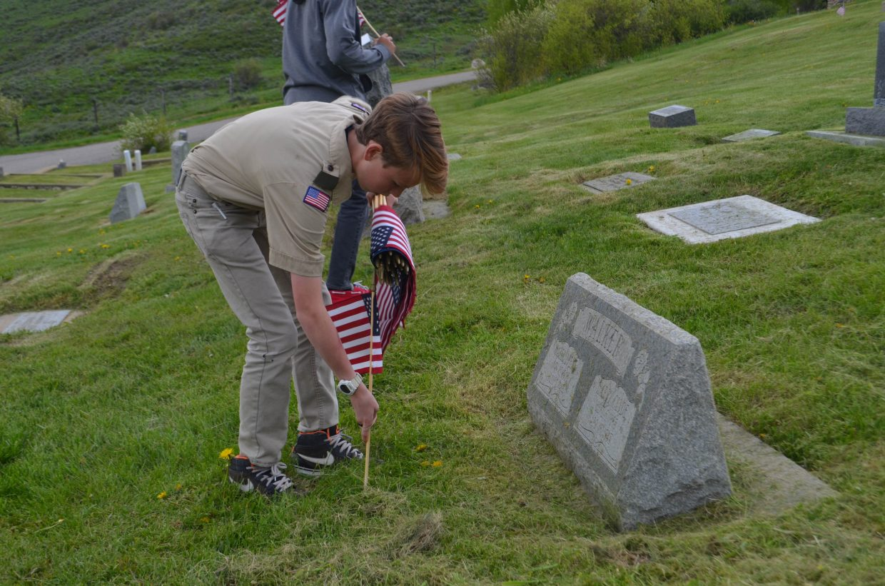Winston Vaughan, a local Boy Scout in Troop 194, places a flag on the grave of a local veteran. Vaughan and his fellow Scouts were placing the flags Thursday afternoon in preparation for Monday's Memorial Day Service.