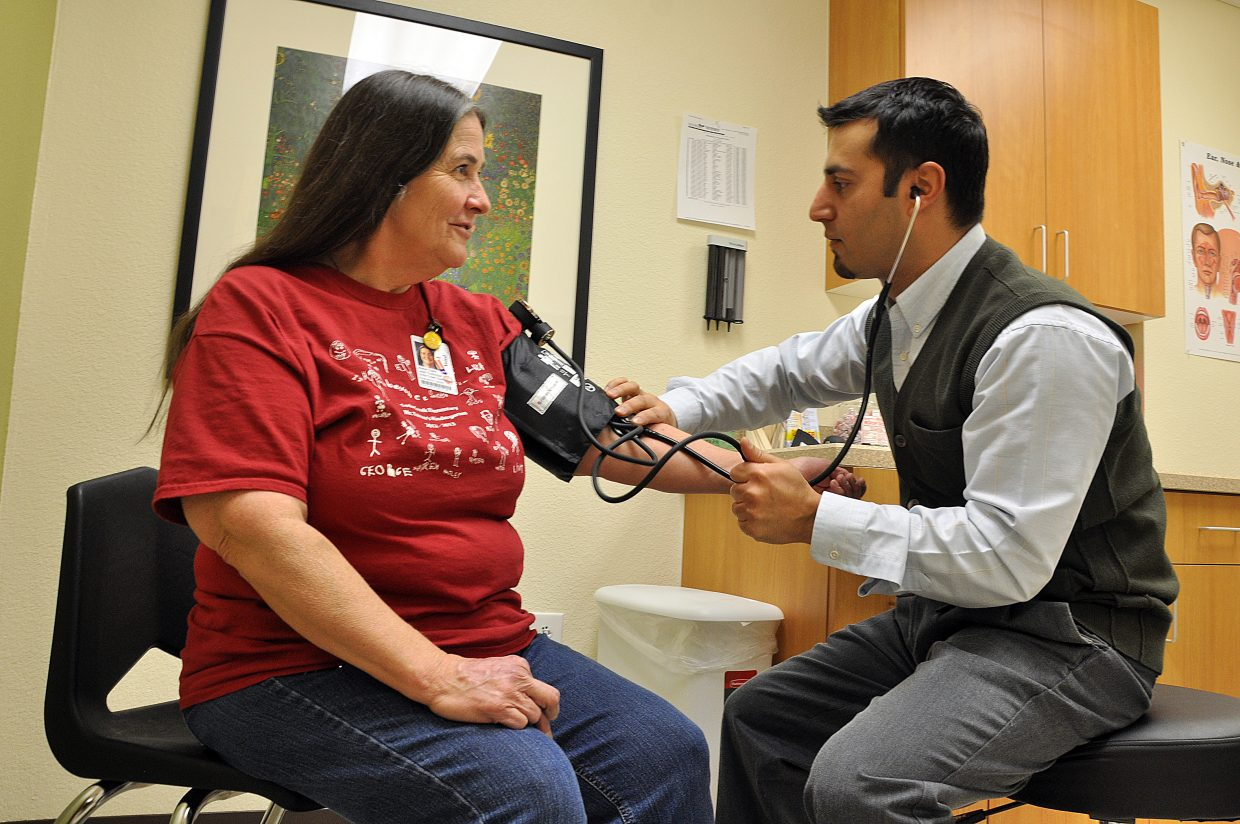 Clinician Milad Shah checks Soda Creek Elementary School custodian Joy Clark's blood pressure at the Steamboat Springs School District's health clinic in 2013. The district is negotiating a contract with YVMC to take over operations of the center.