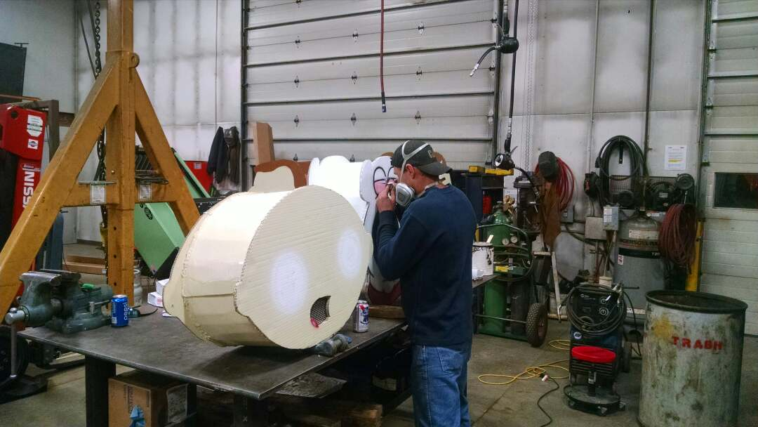 Rpb Norton airbrushes the masks for his team's Family Guy craft for the 2016 Cardboard Classic.