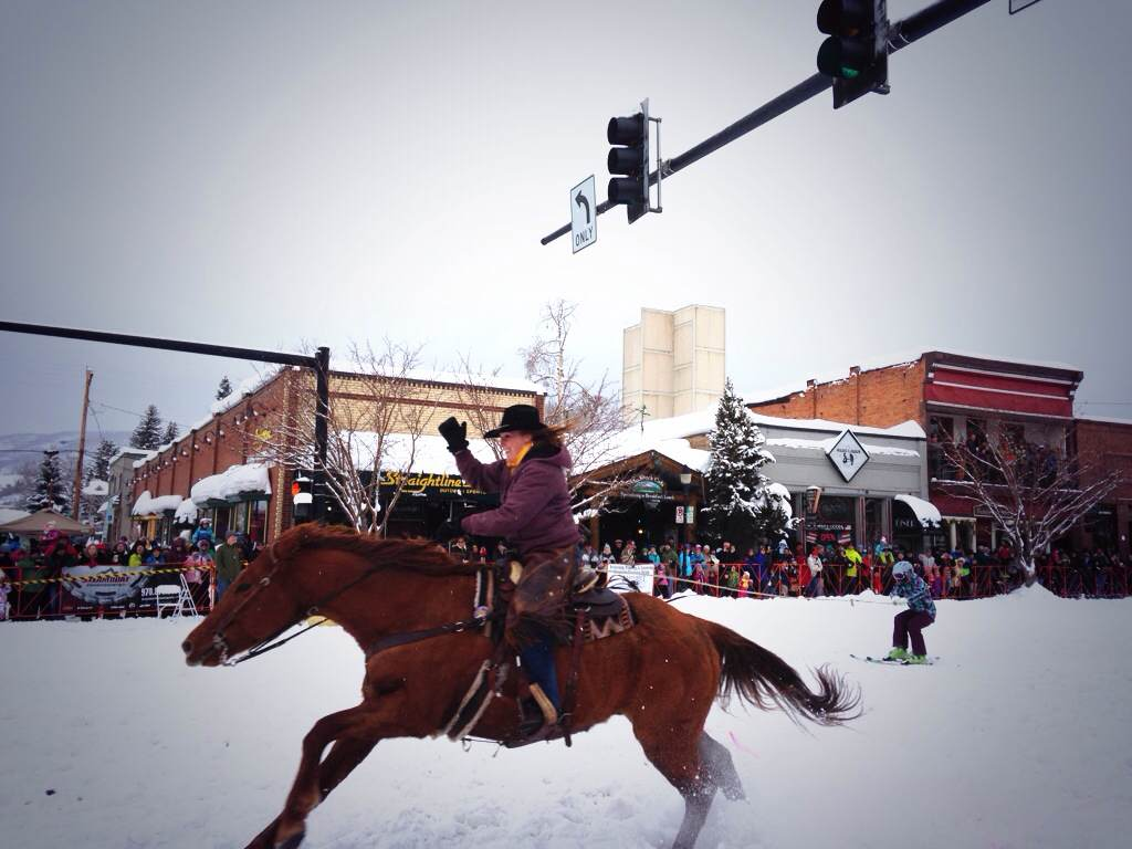 Horseback rider Shealynne Yeager pulls skier Alexa Paoli down Lincoln Avenue during the 101st Winter Carnival street events.