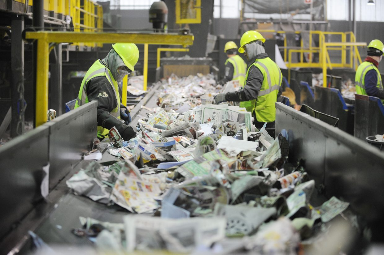 Workers sort through single-stream recycling at Waste Management's Franklin Street materials recovery facility.