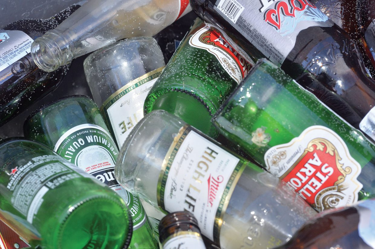 Glass bottles fill a recycling container.