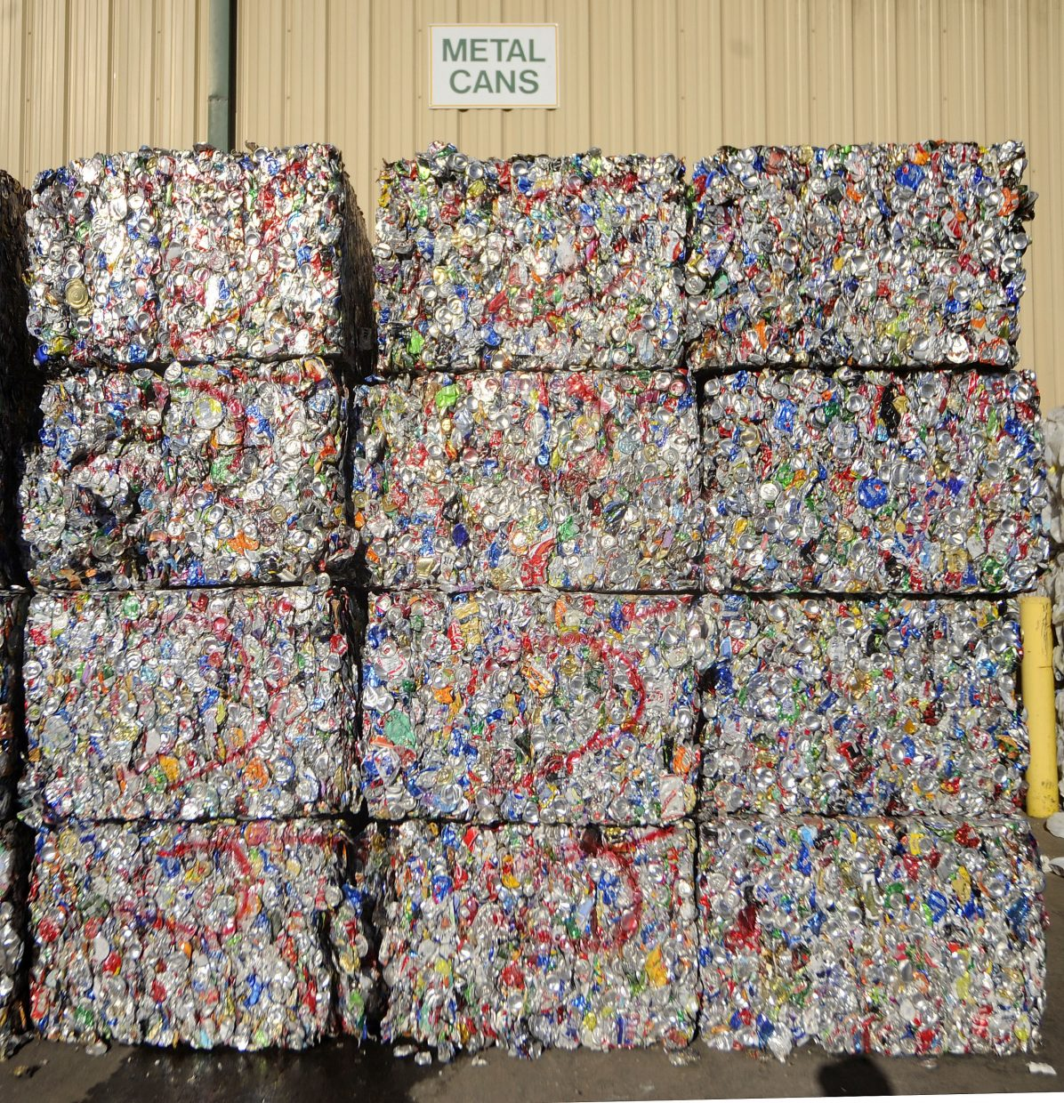 Bales of aluminum cans are stacked in the year at Waste Management's Franklin Street materials recovery facility.