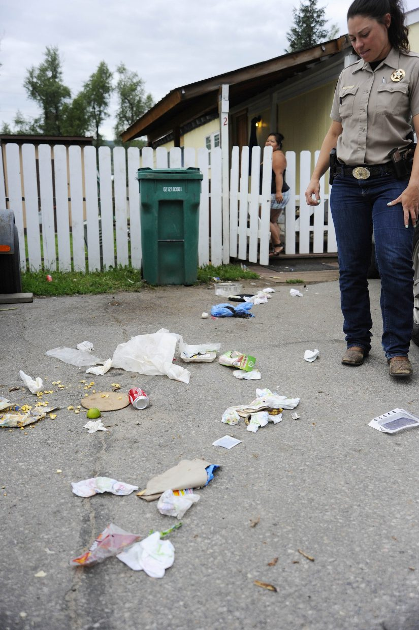 Colorado Parks and Wildlife district wildlife manager Andrea Sponseller looks at trash after speaking with a resident at Dream Island mobile home park.