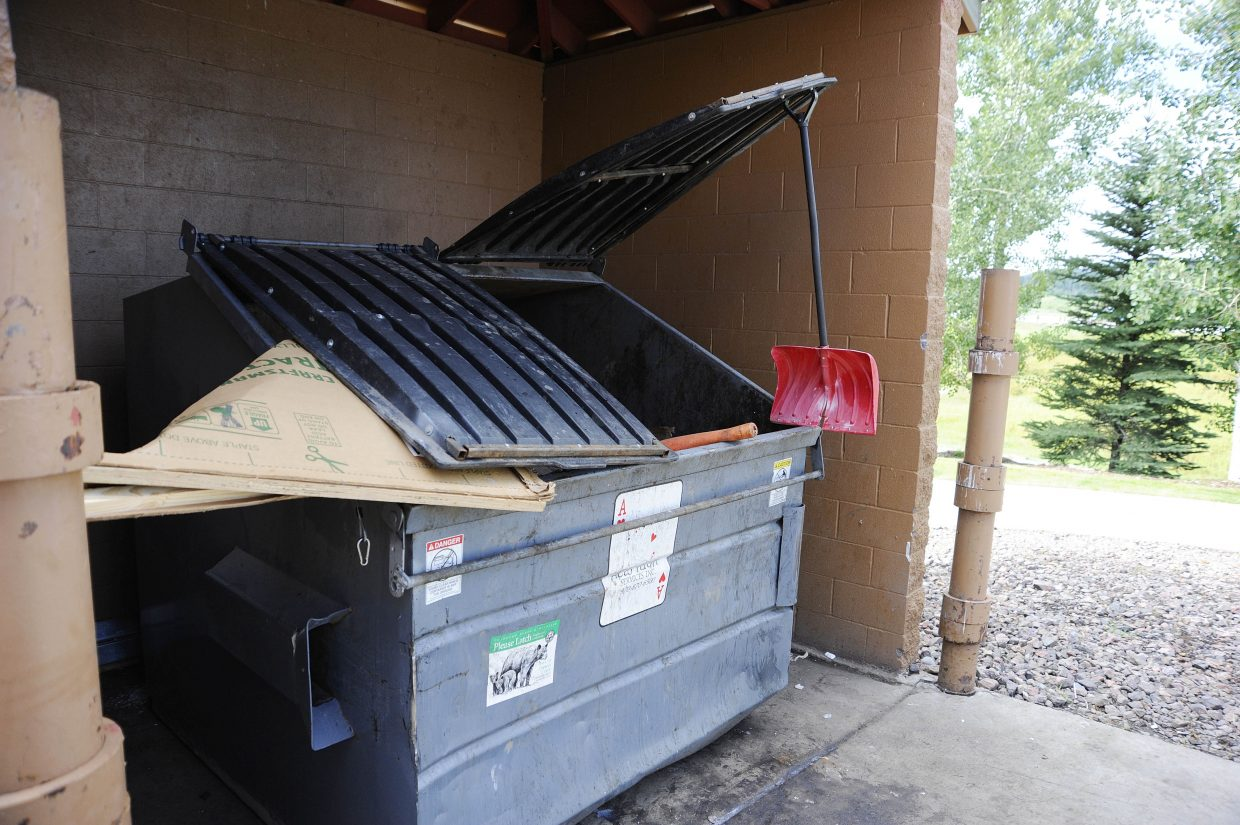 A dumpster is left propped open with a shovel in Central Park Plaza.