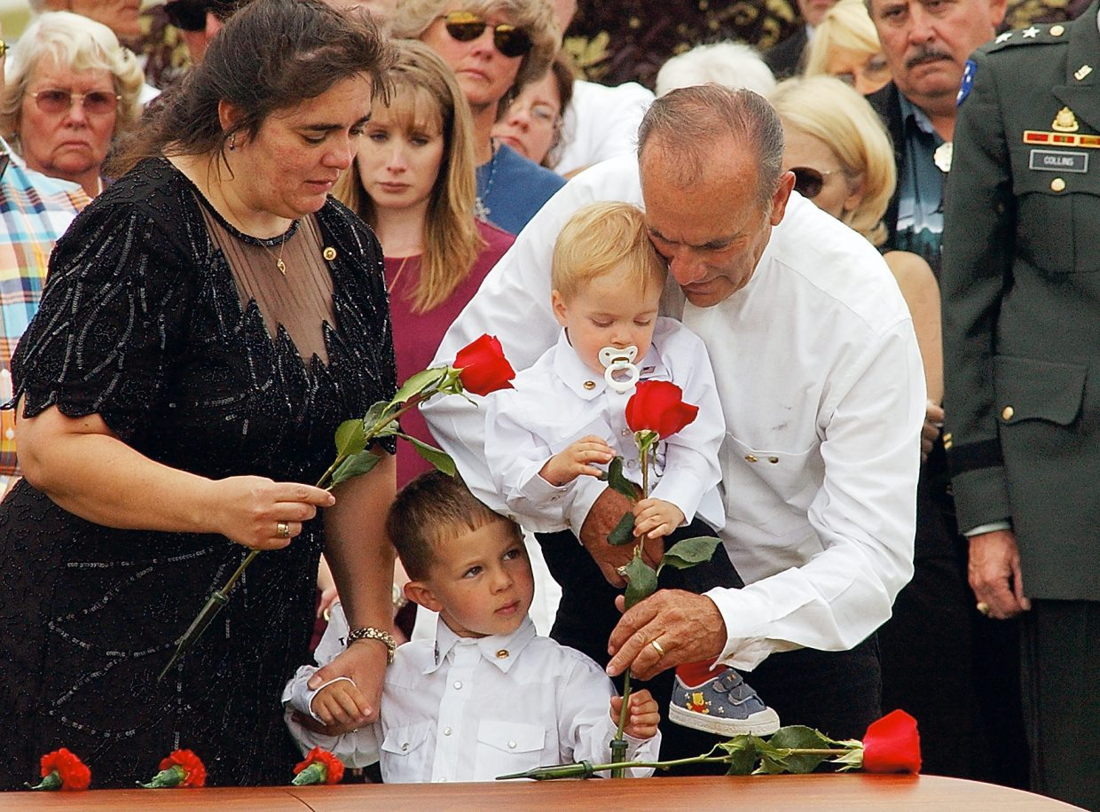 Sherri Lawton and her father, Louis Holloway, help Sherri's sons — Dustin, 4, and Tanner, 1 — place flowers on the casket of the boys' father, staff Sgt. Mark Lawton, during a funeral service in Hayden. Mark Lawton was killed while serving in Iraq. The photograph was taken by John F. Russell and appeared in the Sept. 6, 2003, edition of the Steamboat Today.