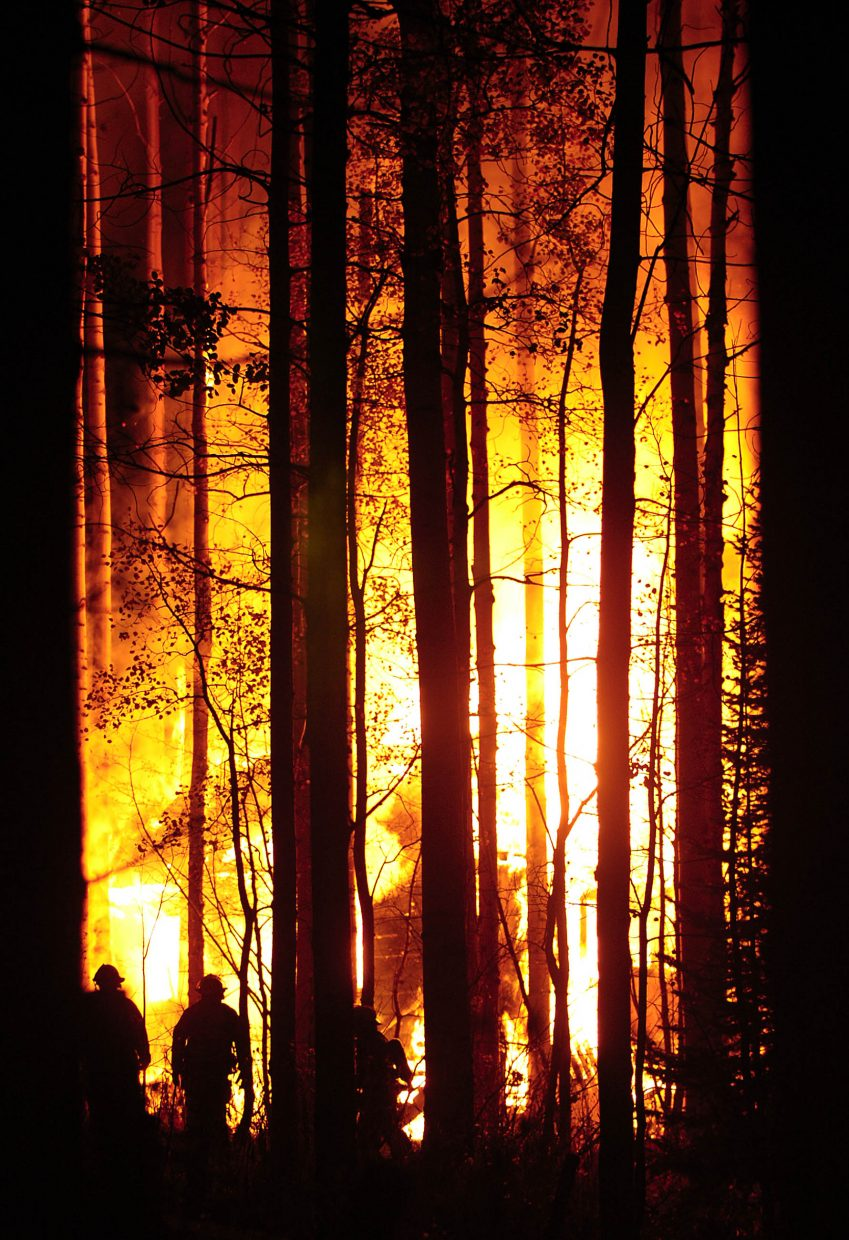 Steamboat Springs Fire Rescue firefighters tend a fire that destroyed a cabin along Routt County Road 36, about 1 mile from the Strawberry Park Hot Springs. The photograph was taken by Matt Stensland and appeared in the Oct. 17, 2008, edition of the Steamboat Today.