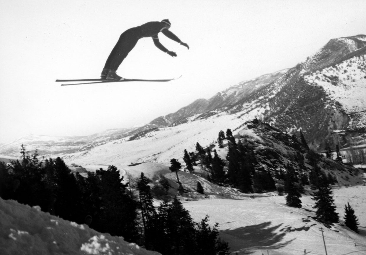 Ski jumping during the first Winter Carnival on Woodchuck Hill, the present site of Colorado Mountain College. Note the Cabin Hotel in the background, now the present site of the Bud Werner Memorial Library.
