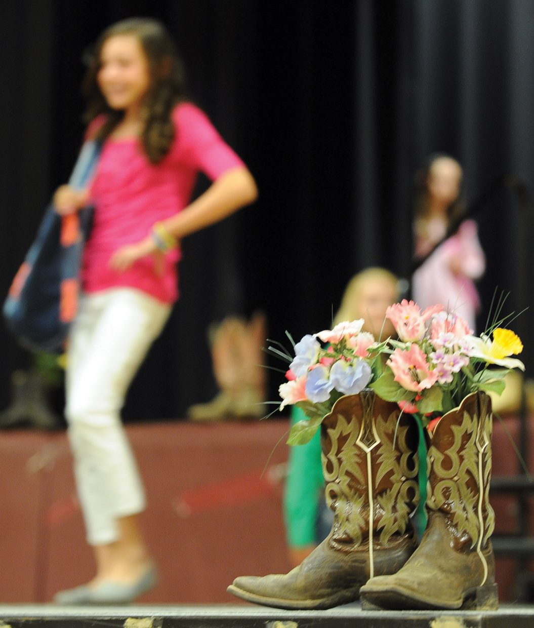 Rachel Koly models behind a pair of boots on a temporary runway set up inside the Soroco High School gym Friday night for the Routt County 4-H Fashion Revue. The revue was part o the Exhibit Day and Fashion Revue put on by the Routt County 4-H. The members had their projects judged and then were able to show them off as part of the revue.