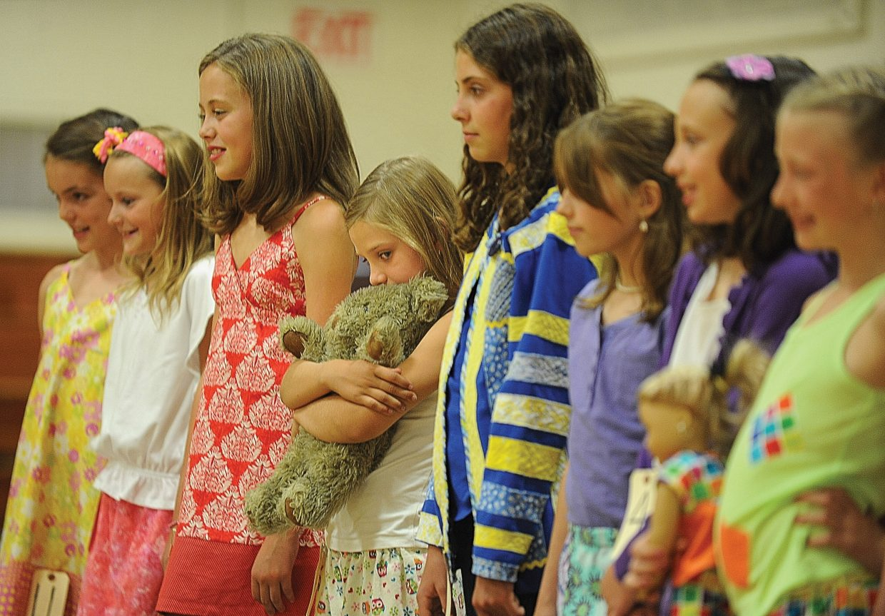 Young Tinsley Wilkinson finds some comfort by hugging her teddy bear during the Routt County 4-H Fashion Revue Friday afternoon at Soroco High School. The revue was part o the Exhibit Day and Fashion Revue put on by the Routt County 4-H. The members had their projects judged and then were able to show them off as part of the revue.
