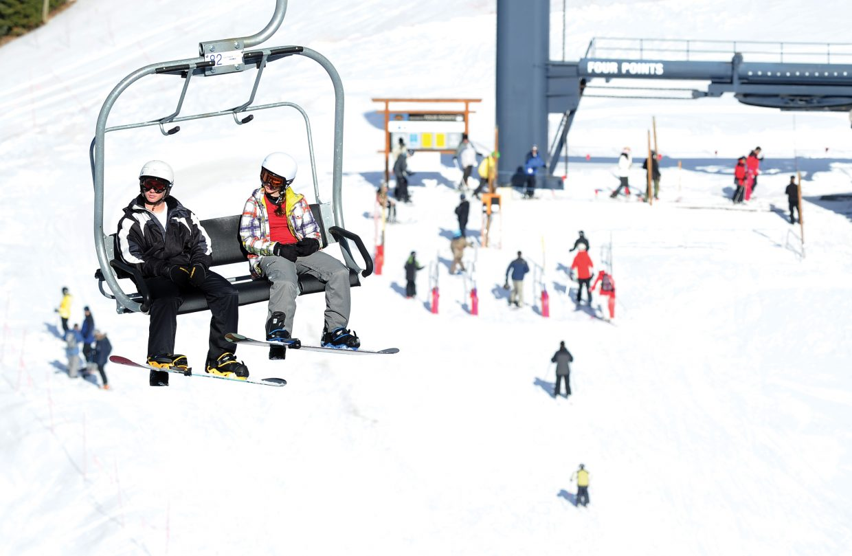 Snowboarders ride up the Burgess Creek lift Friday afternoon at Steamboat Ski Area.