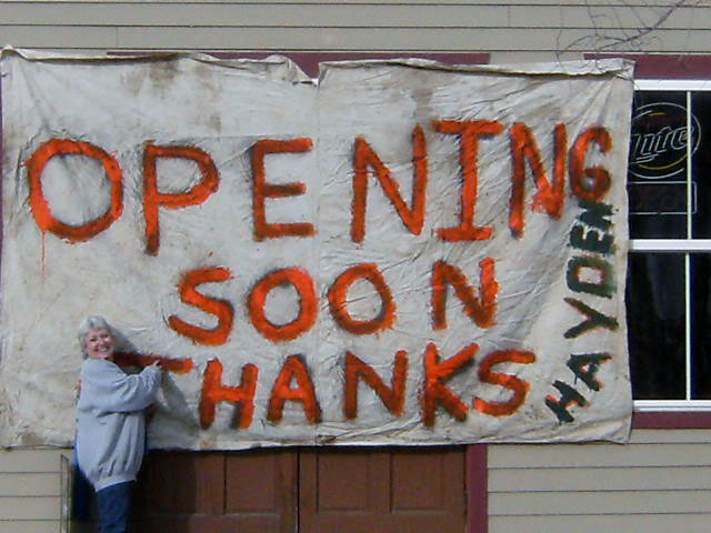 Fawna Odom poses with a sign announcing that she plans to reopen the HiWay Bar in Hayden sometime this month. A community fundraiser allowed Odom to take possession of the bar back from the Colorado Department of Revenue.