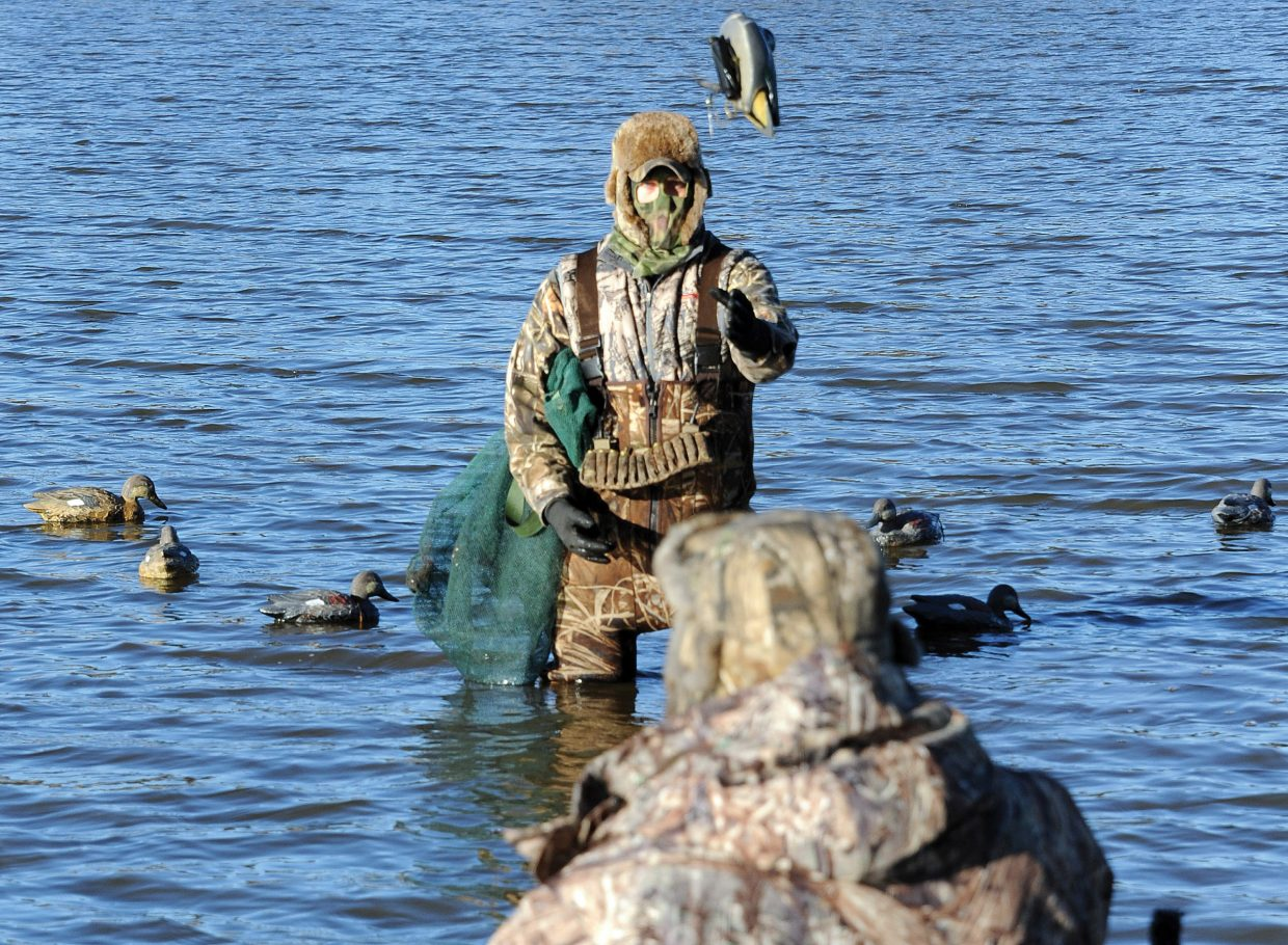 Dean Leahy, top, tosses a duck decoy to Phil Leahy after a December duck hunt in Kansas.