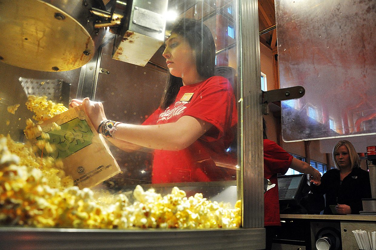 Eva Grant fills a bag of popcorn Thursday for moviegoer Cassidy Bush at Wildhorse Stadium Cinemas. The movie theater was one of several Steamboat businesses to report higher holiday traffic this year because of snow conditions on Mount Werner.