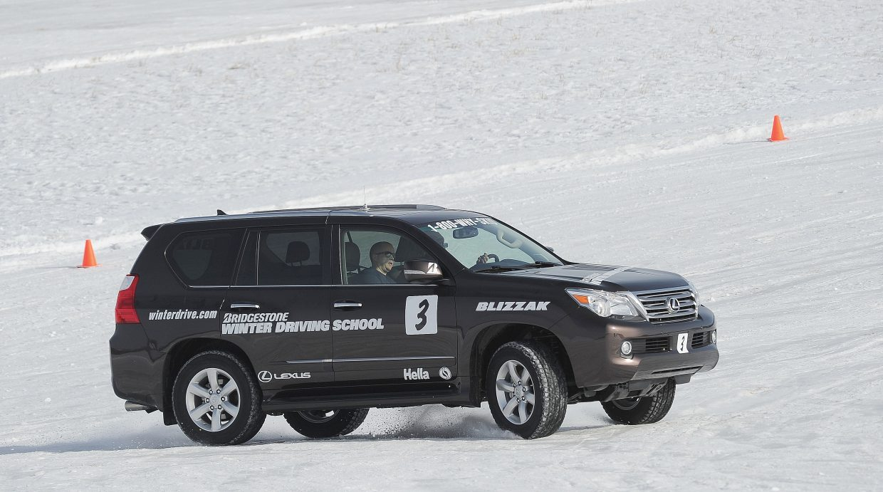 Driver Phylliss Johnson and passenger Neil Mallinson complete a turn on an icy corner during a safety class at the Bridgestone Winter Driving School.