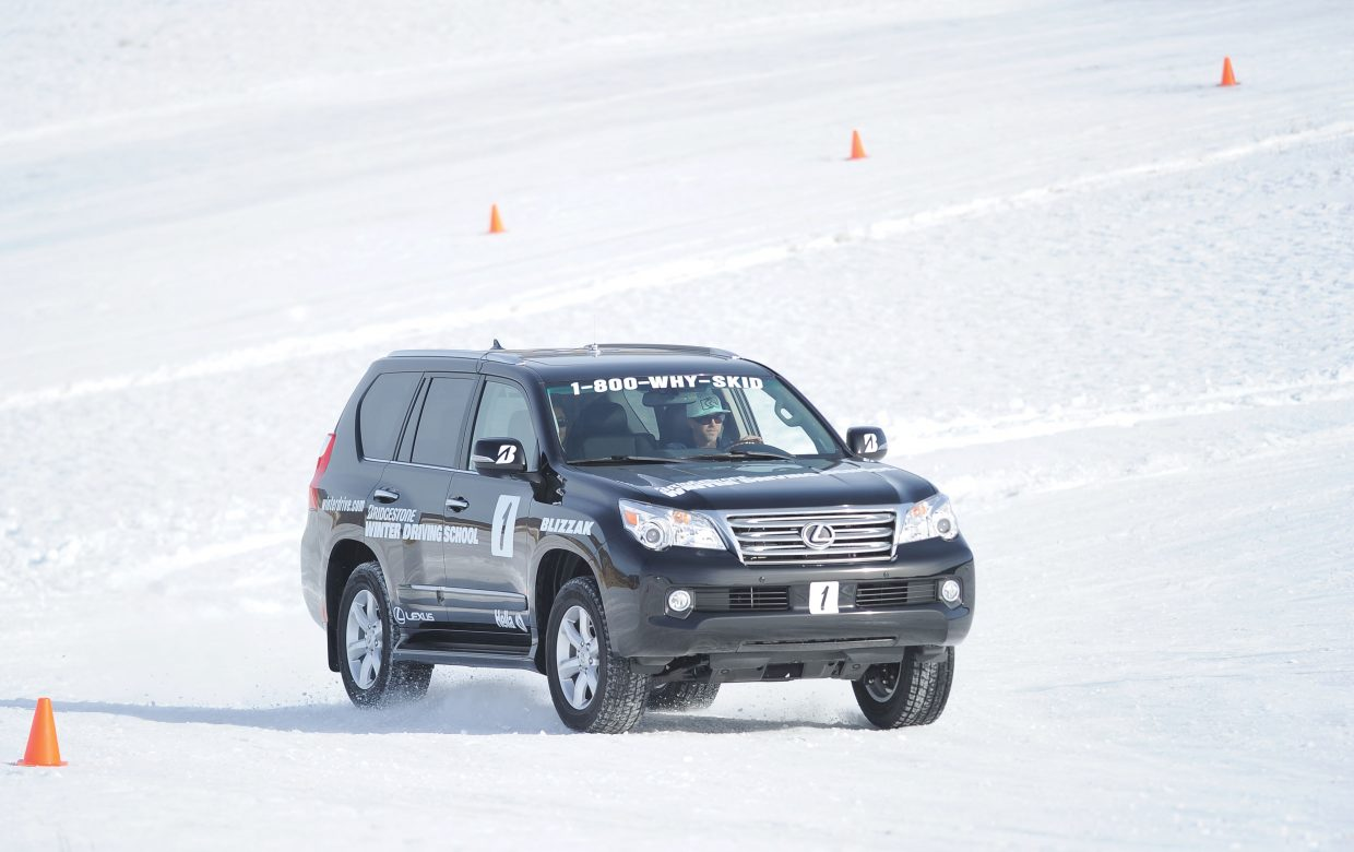 John Russ guides his vehicle through an icy corner at the Bridgestone Winter Driving School.