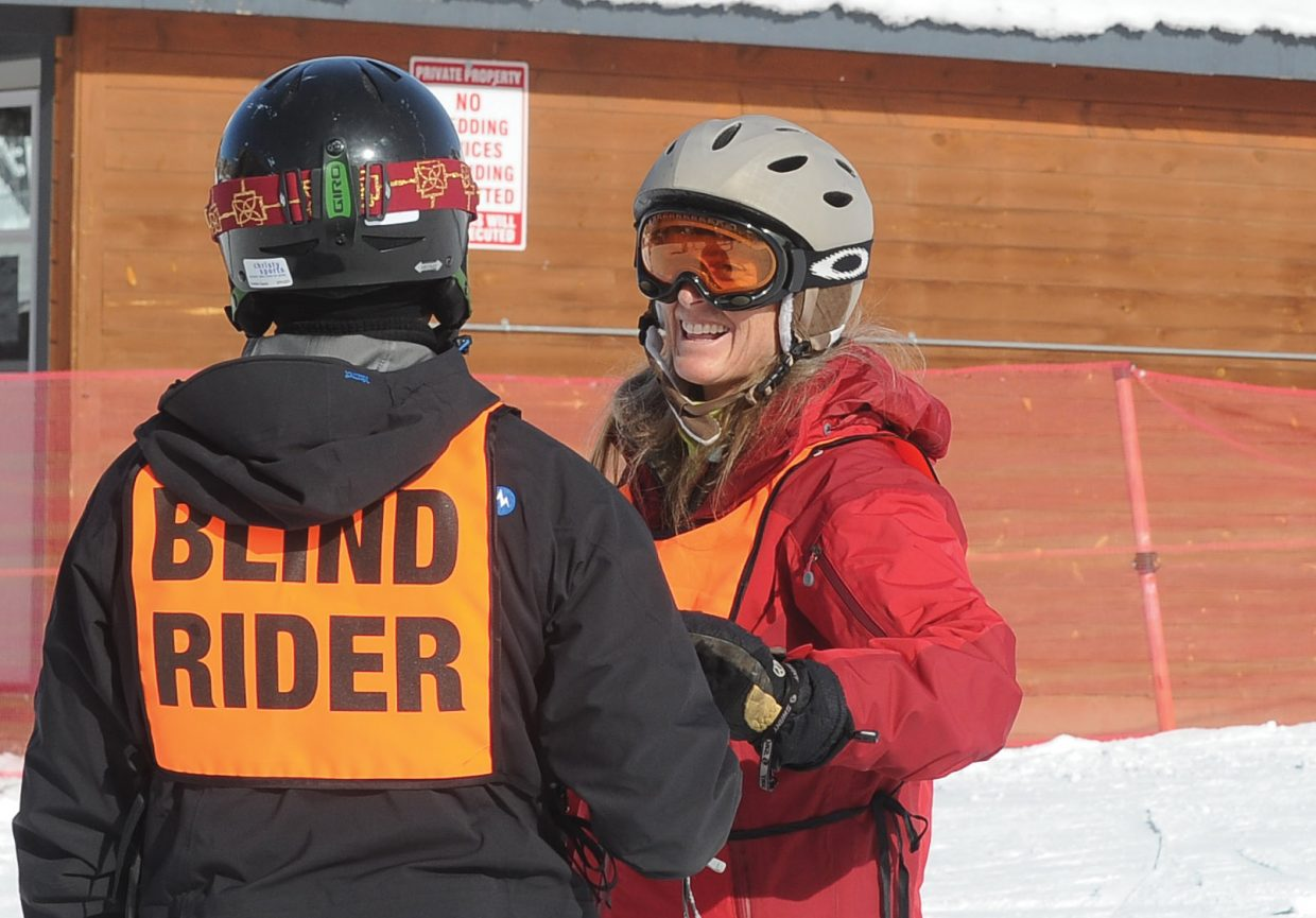 STARS instructor Sheila Farny shares a laugh with veteran Steve Baskis while teaching him to snowboard on a beginners run at Steamboat Ski Area on Monday afternoon.