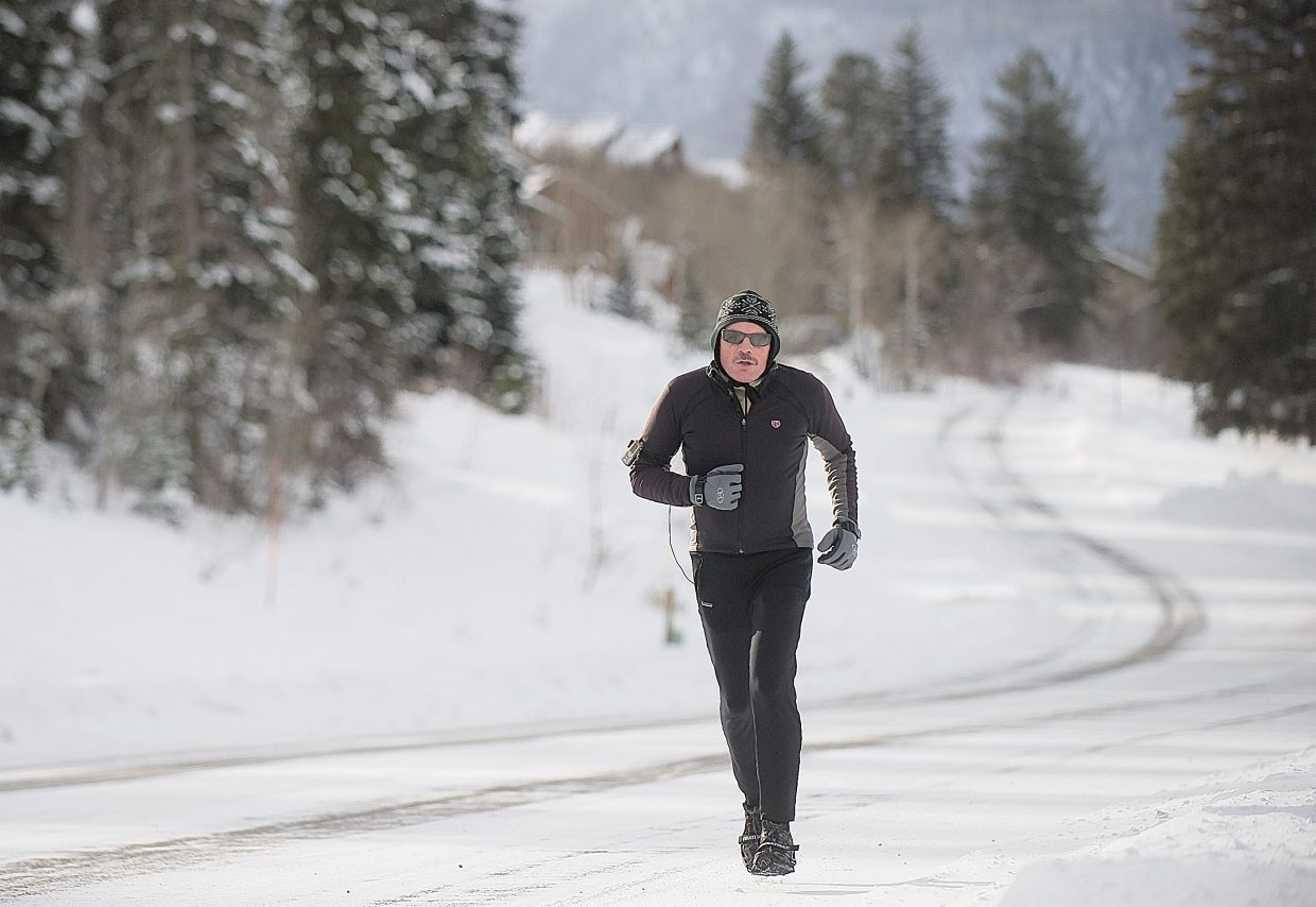 David Kraus makes his way along Steamboat Boulevard on Wednesday afternoon. The local runner said he bundled up for the chilly conditions outside and strapped some traction cleats to his shoes for better grip during some of the longer climbs on the icy roads.