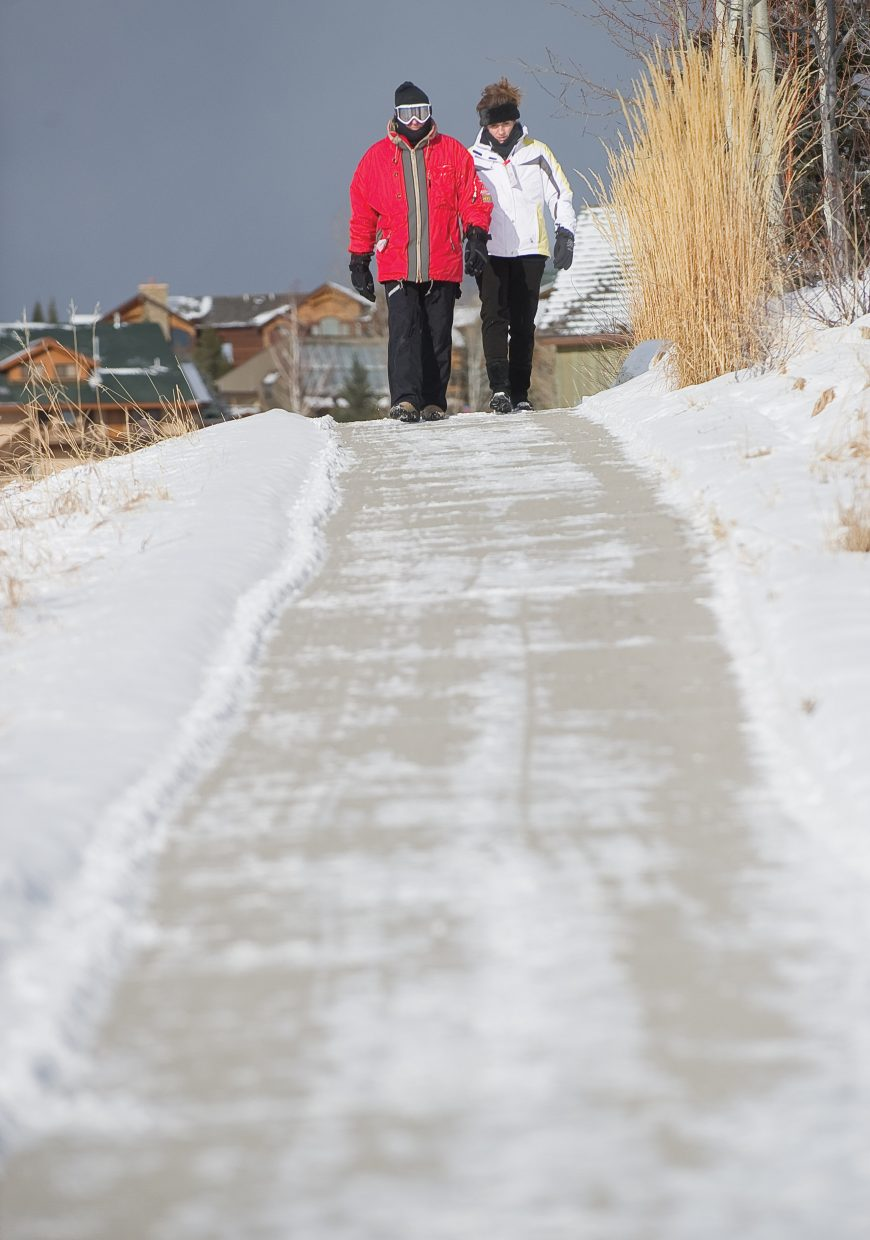 Jeff and Catherine Wallace stroll along a sidewalk Wednesday on Steamboat Boulevard near Mount Werner Circle in Steamboat Springs. The couple was visiting from Florida and was dressed for the chilly conditions after a storm front brought a small amount of snow, and much cooler temperatures, to the area.
