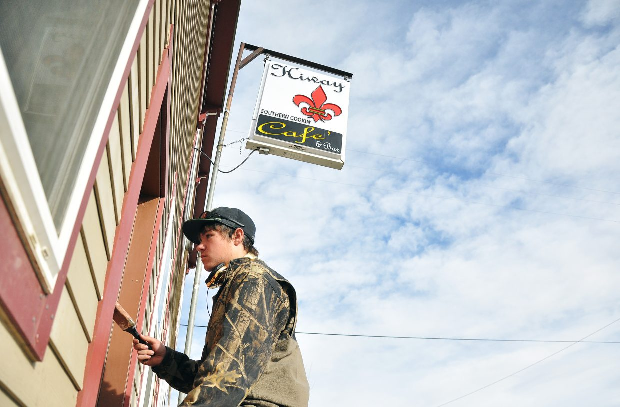 Garrett O'Hanlon paints the front door of the HiWay Bar on Sunday. The bar, which was closed Dec. 22 by the Colorado Department of Revenue for nonpayment of sales taxes, reopened Thursday.