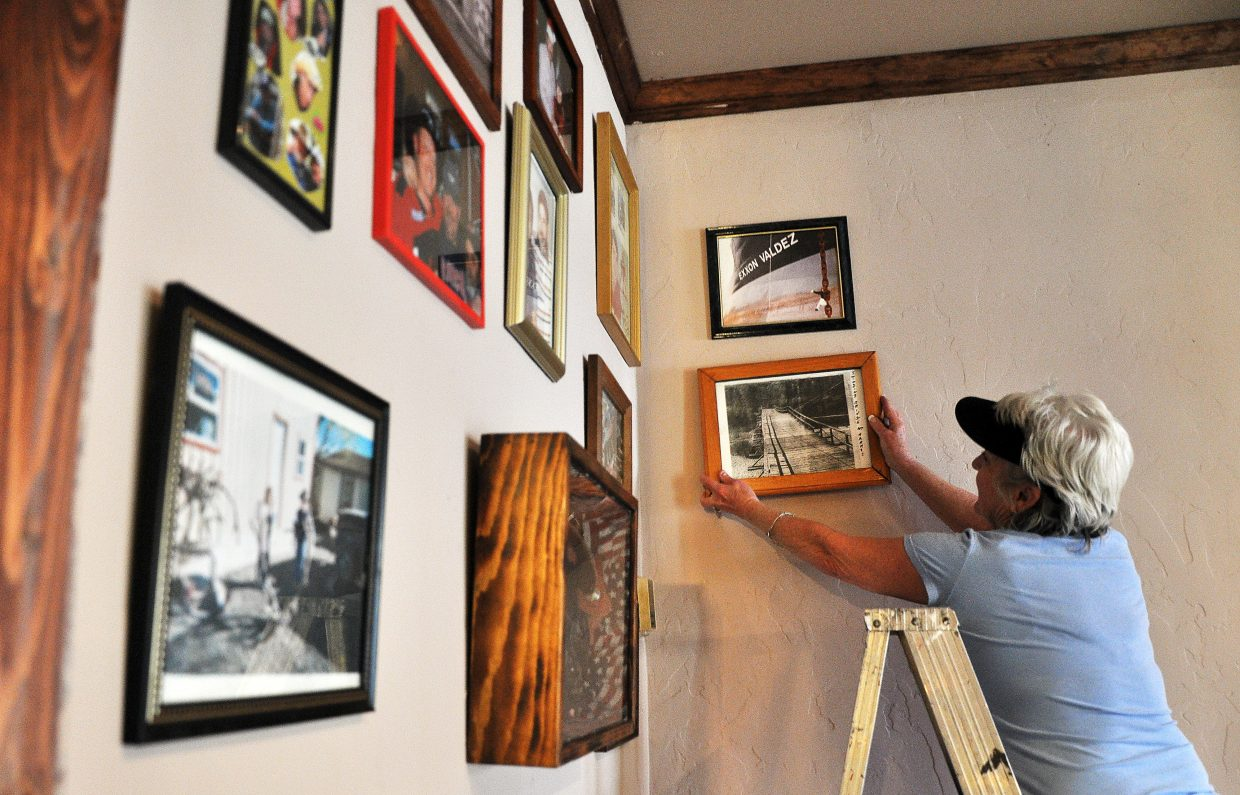 HiWay Bar owner Fawna Odom hangs up an old photograph in the bar on Sunday.