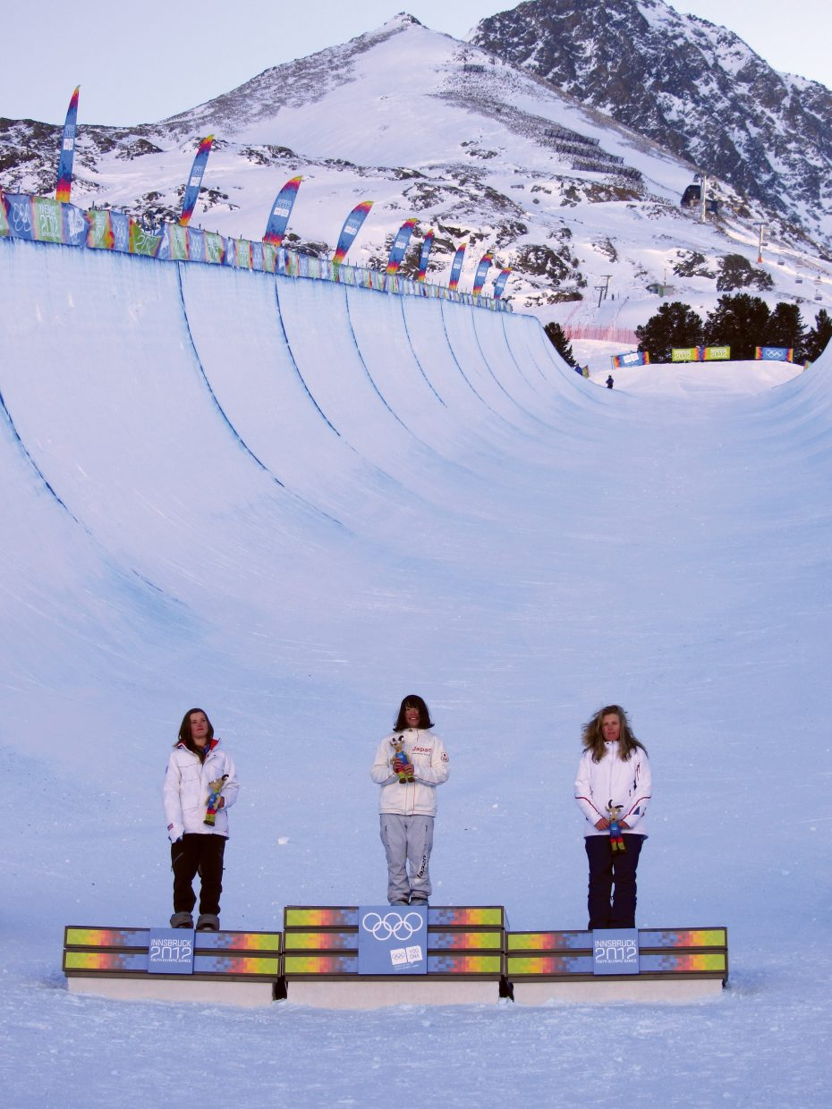 Steamboat Springs snowboarder and silver medalist Arielle Gold, left, gold medalist Hikaru Ohe, of Japan, and bronze medalist Lucile Lefevre, of France, pose for group pictures during the victory ceremony for women's snowboard halfpipe Sunday at the 2012 Winter Youth Olympic Games in Innsbruck, Austria. Gold won the United States' first medal.