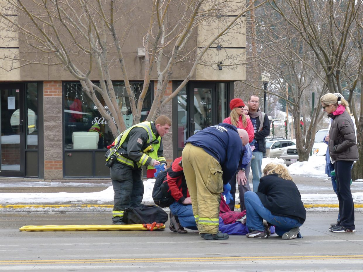 Steamboat Springs Fire Rescue emergency responders aid a 53-year-old Texas woman after a car struck her just after 11 a.m. Saturday at Fifth Street and Lincoln Avenue.