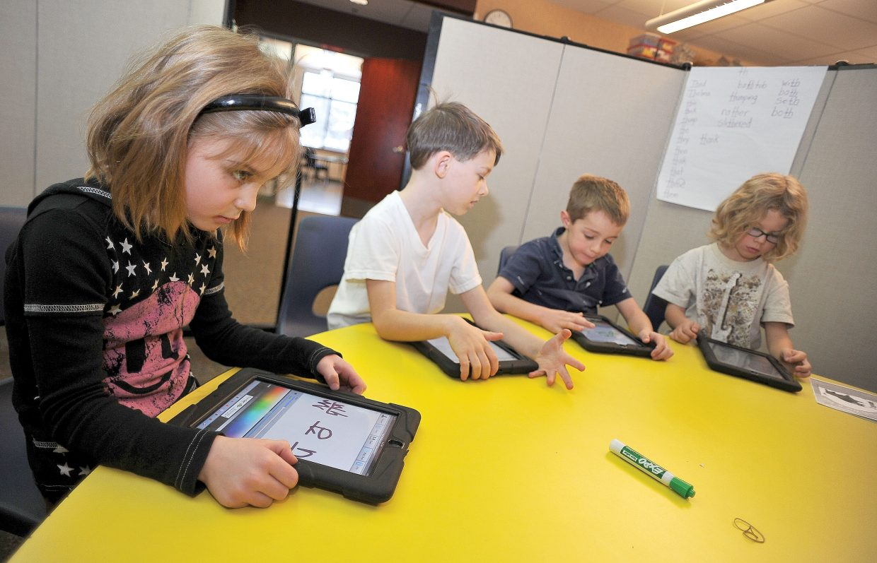 First-grader Avery Duty uses an iPad to complete a lesson in spelling at Soda Creek Elementary School.