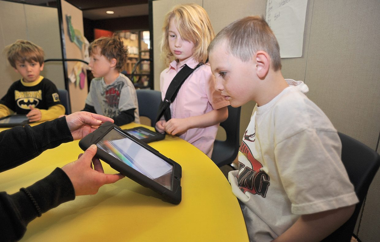 First-grader Austin Moore checks out an iPad on Friday at Soda Creek Elementary School. The iPads are used to help the students with spelling.